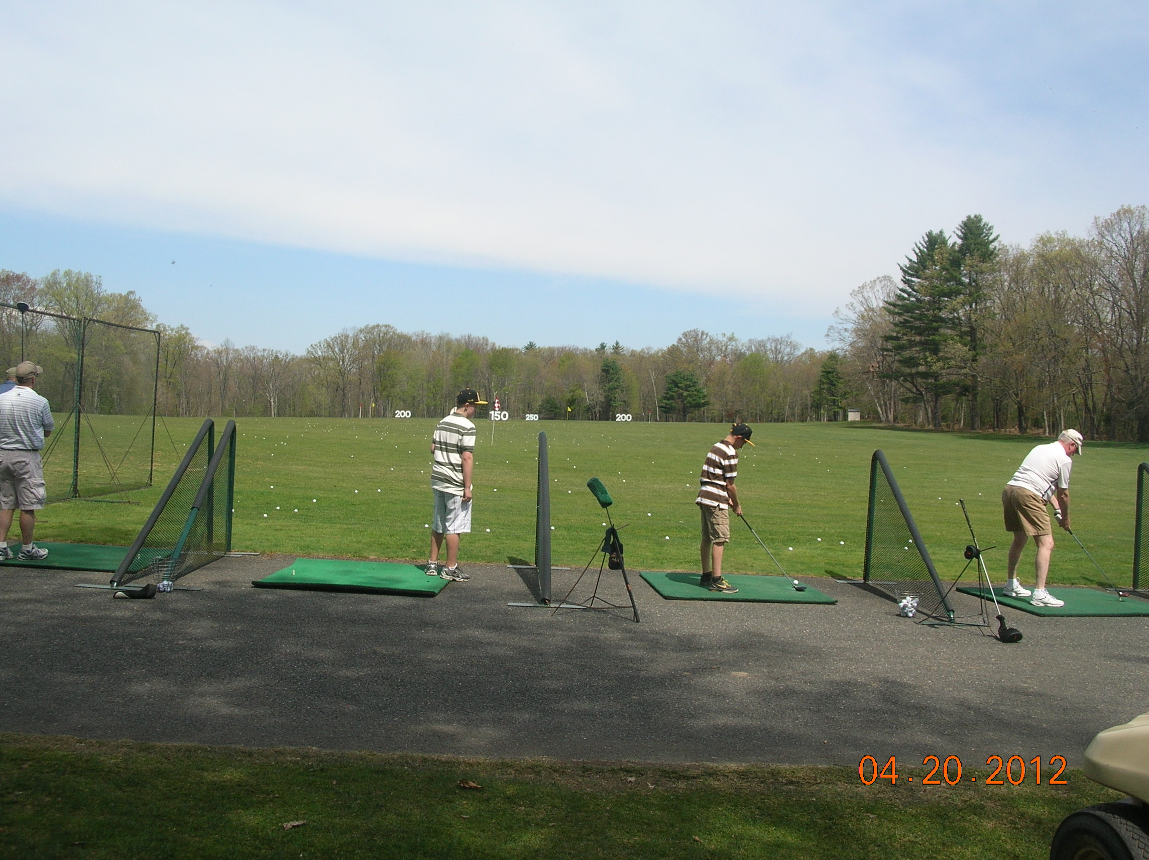 Driving range with booths and grass area to hit from.